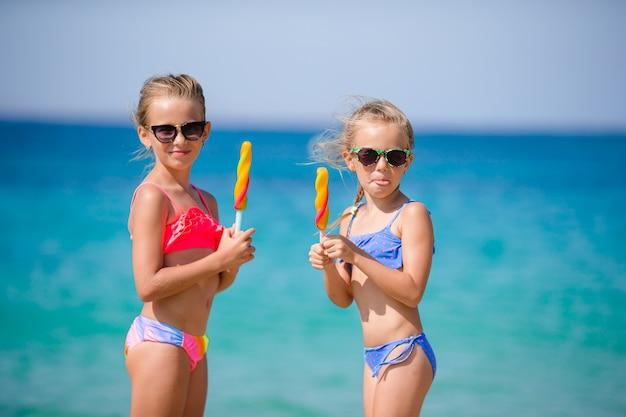 Szczęśliwe Małe Dziewczynki Je Lody Podczas Wakacji Na Plaży. Koncepcja Ludzie, Dzieci, Przyjaciół I Przyjaźni Premium Zdjęcia