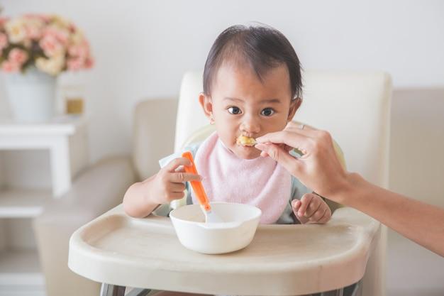 Szczęśliwe Młode Dziecko W Krzesełku Jest Karmione Premium Zdjęcia