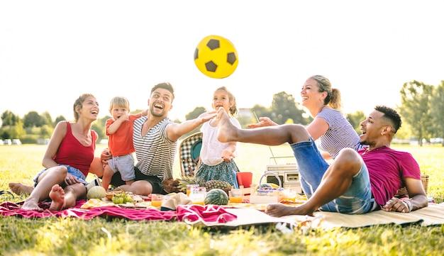 Szczęśliwe Rodziny Wielorasowe Bawiące Się Z Uroczymi Dziećmi Na Piknikowym Przyjęciu W Ogrodzie Premium Zdjęcia