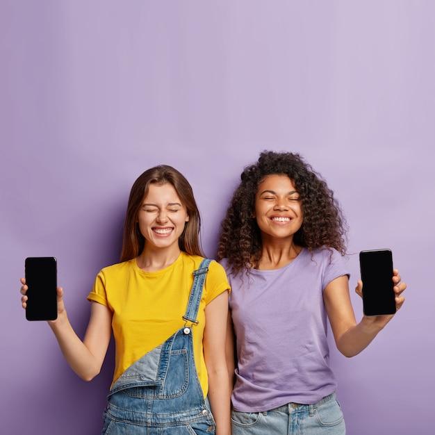 Szczęśliwe, Różnorodne Siostry Stoją Obok Siebie, Pokazują Telefony Komórkowe Z Pustymi Ekranami, Pozytywnie Wyglądają, Reklamują Nowe Gadżety Darmowe Zdjęcia