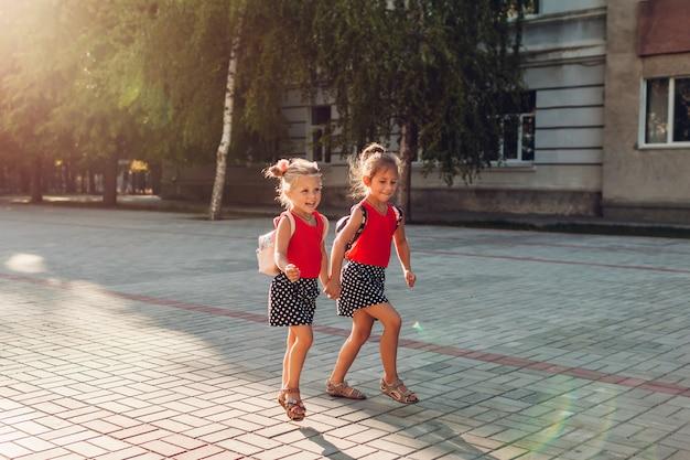 Szczęśliwe siostry dziewczyny są ubranym plecaki i biegają. dzieci uczniowie bawią się w pobliżu szkoły. edukacja Premium Zdjęcia