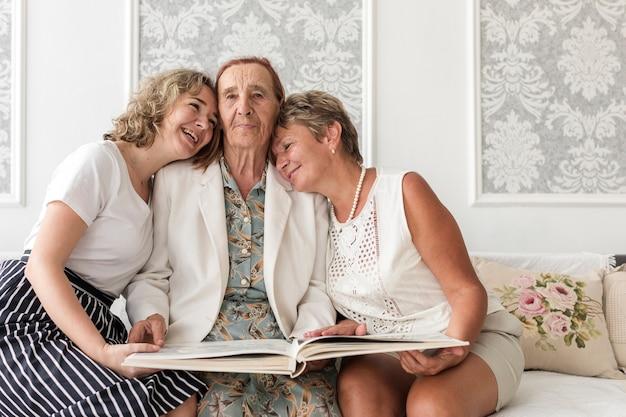 Szczęśliwe trzy pokolenie kobiety siedzi na kanapie z mienie albumem fotograficznym Darmowe Zdjęcia