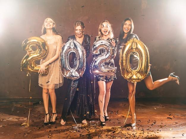 Szczęśliwe, Wspaniałe Dziewczyny W Stylowych Seksownych Sukienkach Posiadających Balony Złote I Srebrne 2020 Darmowe Zdjęcia