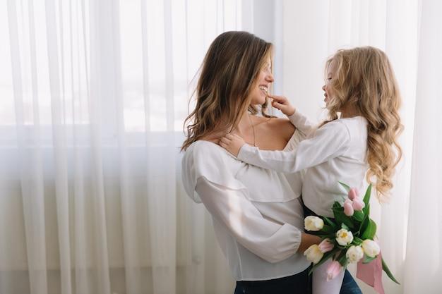 Szczęśliwego Dnia Matki. Córka Dziecka Gratuluje Mamom I Daje Jej Kwiaty Tulipanów. Premium Zdjęcia