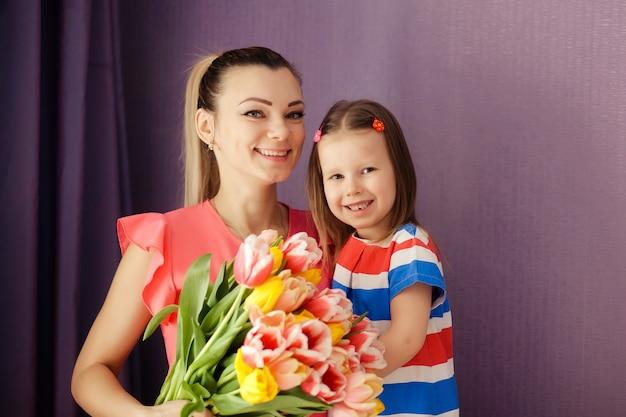 Szczęśliwego Dnia Matki! Córka Gratuluje Mamie I Daje Bukiet Kwiatów Tulipanom. Szczęśliwe Dzieci I Rodzice, Rodzina. Premium Zdjęcia
