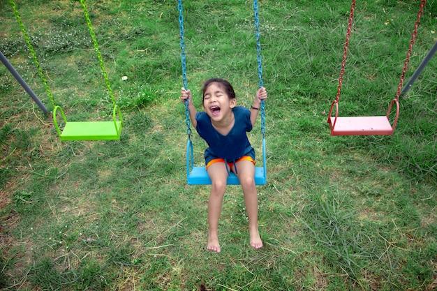 Szczęśliwej Azjatykciej Dzieciak Sztuki Huśtawki Plenerowy Playpark Premium Zdjęcia