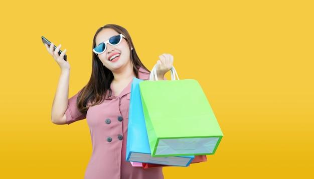 Szczęśliwej azjatykciej kobiety przypadkowi ubrania trzyma kredytową kartę i torba na zakupy na jasnożółtym. Premium Zdjęcia