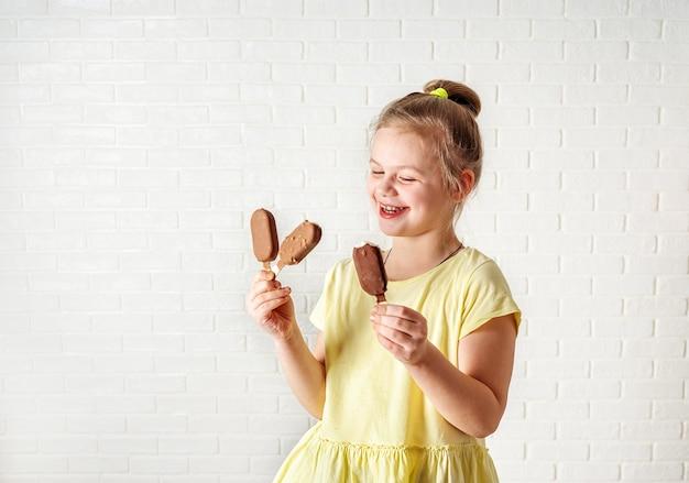 Szczęśliwej Małej Dziewczynki łasowania Lody Popsicles Przy Lato Czasem Premium Zdjęcia