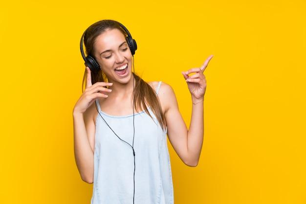Szczęśliwej Młodej Kobiety Słuchająca Muzyka Nad Odosobnionym Kolor żółty ściany śpiewem Premium Zdjęcia