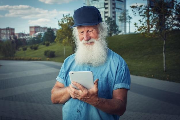 Szczęśliwej Starości. Siwy Zaawansowany Starzec, Emeryt Z Uśmiechem Używa Tabletu. Premium Zdjęcia