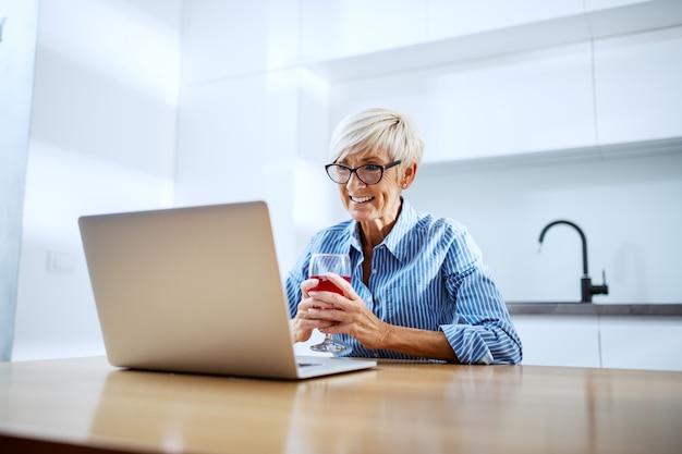 Szczęśliwej Uśmiechniętej Blondynki Starszy Kobiety Obsiadanie Przy łomotać Stół, Pijący Czerwone Wino I Mieć Wideo Rozmowę Przy Laptopem Premium Zdjęcia