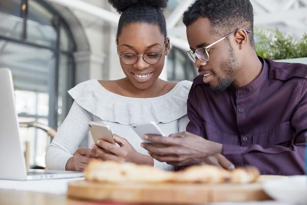 Szczęśliwi Afroamerykańscy Przedsiębiorcy Opracowują Nową Strategię Biznesową Na Przenośnym Laptopie, Używają Telefonów Komórkowych Do Przeglądania Informacji W Internecie Darmowe Zdjęcia