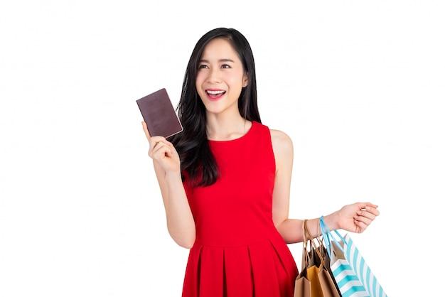 Szczęśliwi Azjatyccy Kobiety Mienia Torba Na Zakupy I Pokazywać Passort W Innej Ręce Premium Zdjęcia