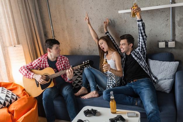 Szczęśliwi Młodzi Ludzie Bawią Się, Impreza Z Przyjaciółmi W Domu, Firma Hipster Razem, Dwóch Mężczyzn, Jedna Kobieta, Gra Na Gitarze, Uśmiechnięta, Pozytywna, Zrelaksowana, Pije Piwo Darmowe Zdjęcia