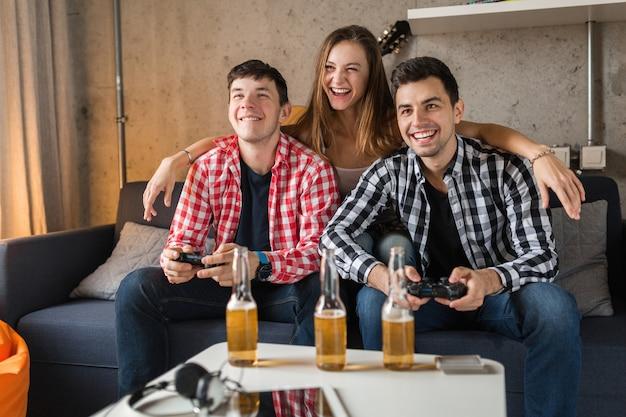 Szczęśliwi Młodzi Ludzie Grający W Gry Wideo, Zabawa, Impreza Z Przyjaciółmi W Domu, Firma Hipster Razem, Dwóch Mężczyzn Jedna Kobieta, Uśmiechnięta, Pozytywna, Zrelaksowana, Emocjonalna, śmiejąca Się, Rywalizacja Darmowe Zdjęcia