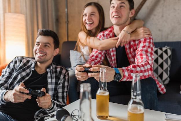 Szczęśliwi Młodzi Ludzie Grający W Gry Wideo, Zabawa, Impreza Z Przyjaciółmi W Domu, Z Bliska Ręce Trzymające Joystick, Firma Hipster Razem, Uśmiechnięta, Pozytywna, śmiejąca Się, Konkurencja, Butelki Piwa Na Stole Darmowe Zdjęcia