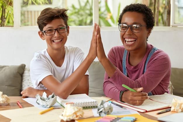 Szczęśliwi Młodzi Partnerzy Współpracują Ze Sobą W Miejscu Pracy, Przybijają Sobie Piątkę, Radują Się Minami, Pracują Nad Badaniami, Zapisują Notatki W Notatniku, Zastanawiają Się Nad Pomysłem, Pracują W Zespole. Darmowe Zdjęcia