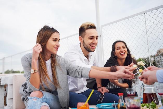 Szczęśliwi Młodzi Przyjaciele Siedzieli Przy Stole I Urządzali Piknik Na świeżym Powietrzu. Darmowe Zdjęcia