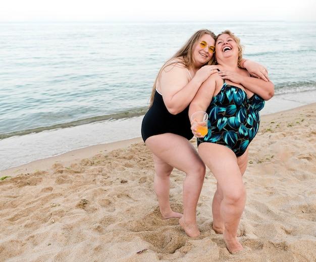 Szczęśliwi Plus Size Przyjaciele Stojący W Piasku Darmowe Zdjęcia