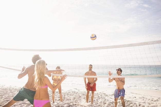Szczęśliwi Przyjaciele Bawić Się Siatkówkę Plażową Premium Zdjęcia