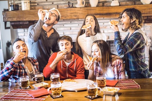 Szczęśliwi Przyjaciele Grupują łasowanie Pizzę Przy Szalet Restauraci Domem Premium Zdjęcia