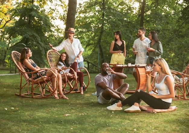 Szczęśliwi Przyjaciele, Jedzenie I Picie Piwa Na Kolację Z Grilla Na Zachód Słońca Darmowe Zdjęcia