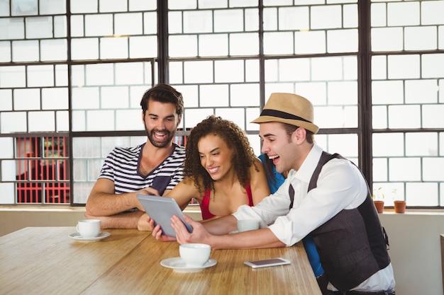 Szczęśliwi Przyjaciele śmia Się Podczas Gdy Patrzejący Pastylkę Premium Zdjęcia