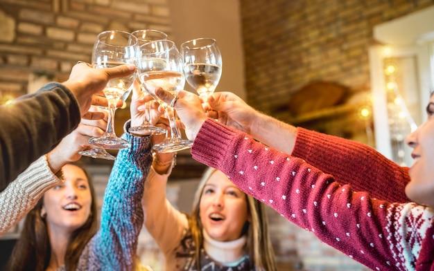 Szczęśliwi przyjaciele świętuje boże narodzenie opiekając szampana wino w domu obiad Premium Zdjęcia