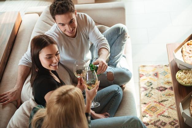 Szczęśliwi Przyjaciele Szczęk Daje Grzanki I Brzęk Szkła Na Kanapie Premium Zdjęcia