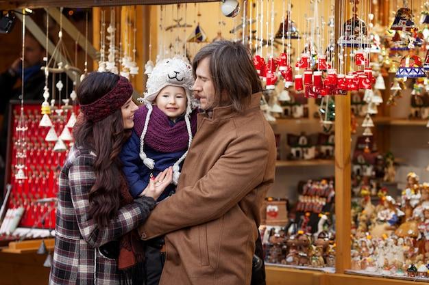 Szczęśliwi rodzice i małe dziecko na tradycyjnym europejskim rynku świątecznym Premium Zdjęcia