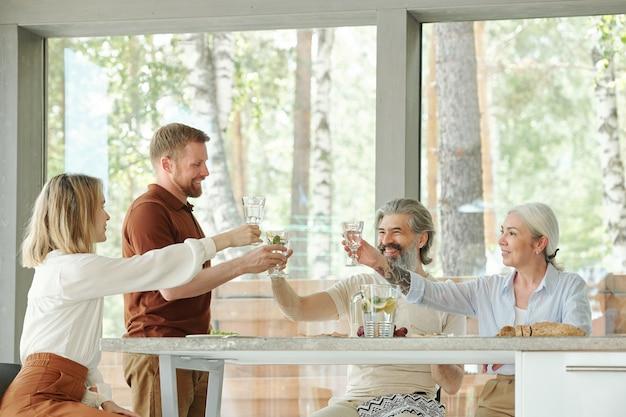 Szczęśliwi Starsi Rodzice I Starsze Dzieci Podnosząc Szklanki Lemoniady Podczas Picia Na Spotkanie Przy Rodzinnym Obiedzie Premium Zdjęcia