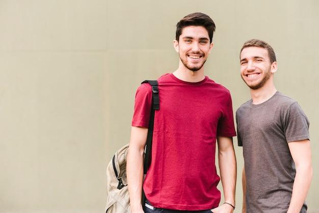Szczęśliwi uśmiechnięci przyjaciele patrzeje kamerę Darmowe Zdjęcia