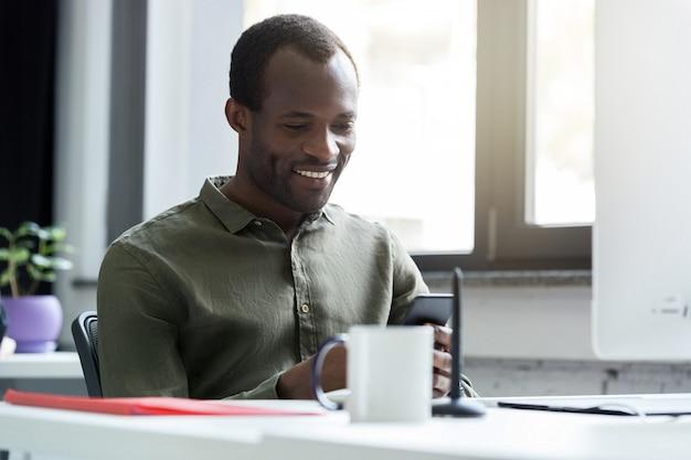 Szczęśliwy Afrykański Mężczyzna Patrzeje Jego Telefon Komórkowego Darmowe Zdjęcia