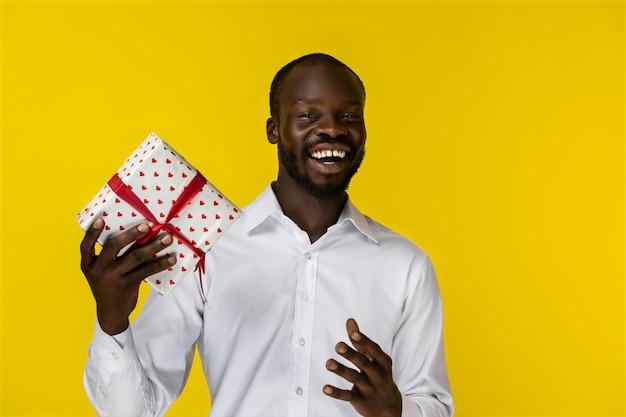 Szczęśliwy Afrykański Mężczyzna Smilling Przy Kamerą I Trzyma Prezent Darmowe Zdjęcia