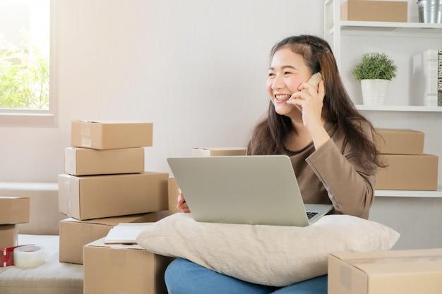 Szczęśliwy Azjatycki Młody Przedsiębiorca, Rozmawiając Na Smartfonie Z Klientem Dla Zamówienia Tack Premium Zdjęcia