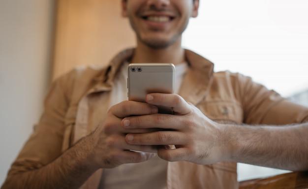 Szczęśliwy Azjatykci Mężczyzna Mienia Telefon Komórkowy, Gawędzenie, Otrzymywa Wiadomość Tekstową, Rezerwuje Bilety, Skupia Się Na Rękach Premium Zdjęcia