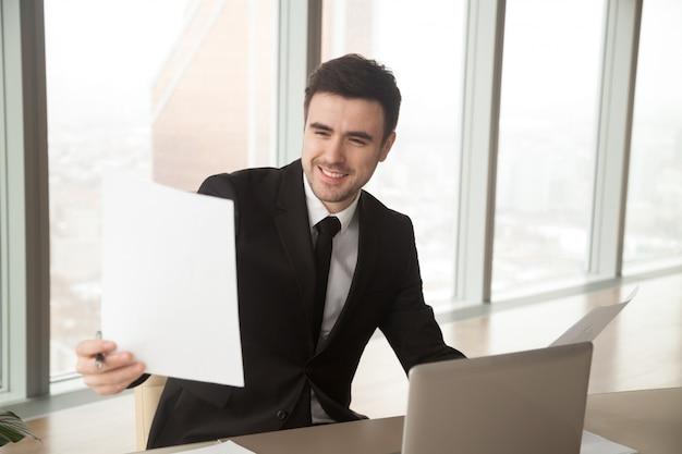 Szczęśliwy biznesmen trzyma pieniężne statystyki raport, satysfakcjonujący Darmowe Zdjęcia