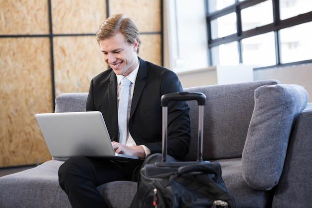 Szczęśliwy biznesmena obsiadanie na kanapie i używać laptopie w biurze Premium Zdjęcia