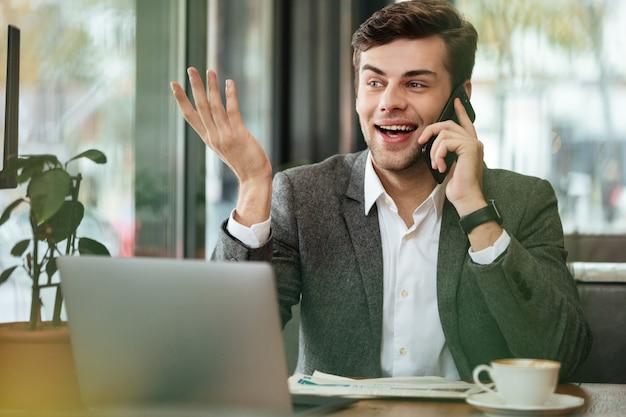 Szczęśliwy Biznesmena Obsiadanie Stołem W Kawiarni Z Laptopem I Opowiadać Smartphone Podczas Gdy Patrzejący Daleko Od Darmowe Zdjęcia