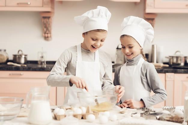 Szczęśliwy chłopiec i dziewczyna miesza jajecznego kucharstwo przy kuchnią. Premium Zdjęcia