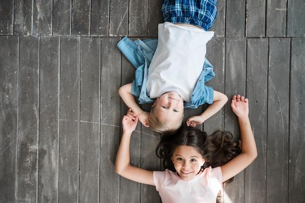 Szczęśliwy chłopiec i dziewczyny lying on the beach na twarde drzewo podłoga Darmowe Zdjęcia