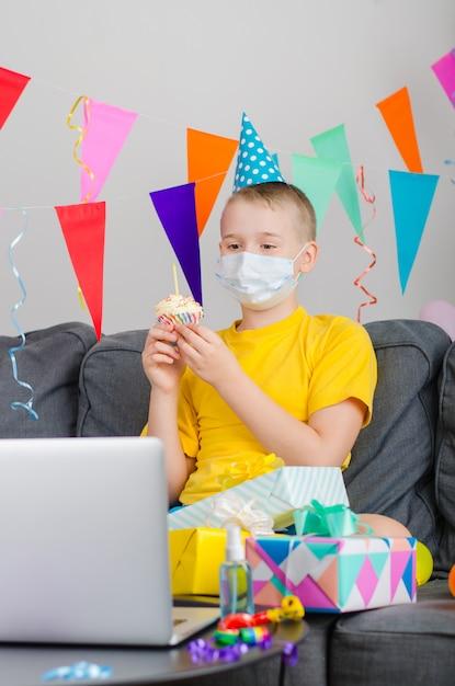 Szczęśliwy Chłopiec W Masce Medycyna Medycyny Obchodzi Urodziny Przez Połączenie Wideo Z Laptopem Premium Zdjęcia