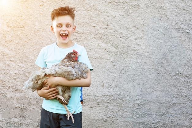 Szczęśliwy chłopiec w niebieskim t-shirt gospodarstwa kurczaka i śmiejąc się na niewyraźne Premium Zdjęcia