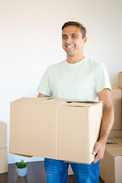 Szczęśliwy Człowiek Posiadający Karton W Swoim Nowym Mieszkaniu Lub Domu Darmowe Zdjęcia