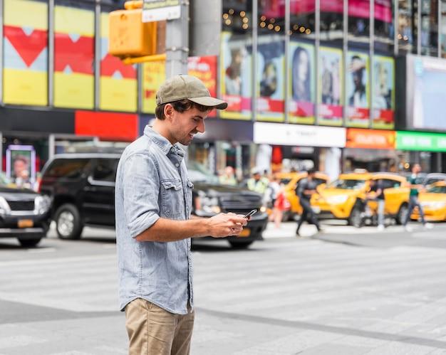 Szczęśliwy człowiek sms-y na swoim smartfonie Darmowe Zdjęcia