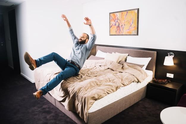 Szczęśliwy człowiek spada na łóżku Darmowe Zdjęcia