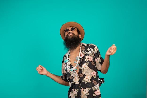 Szczęśliwy człowiek z długą brodą w kapeluszu i pasiastą koszulą z niebieskim gestem. Darmowe Zdjęcia