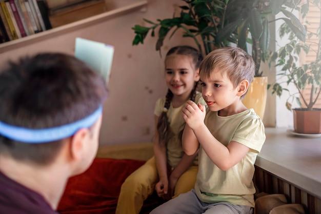 Szczęśliwy Dorosły Ojciec Gra W Grę Planszową Z Dwójką Dzieci W Domowym Wnętrzu, A Właściwie Wartości Rodzinne Premium Zdjęcia