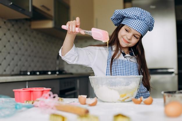 Szczęśliwy Dzieciak Dziewczyna Wyrabia Ciasto Premium Zdjęcia