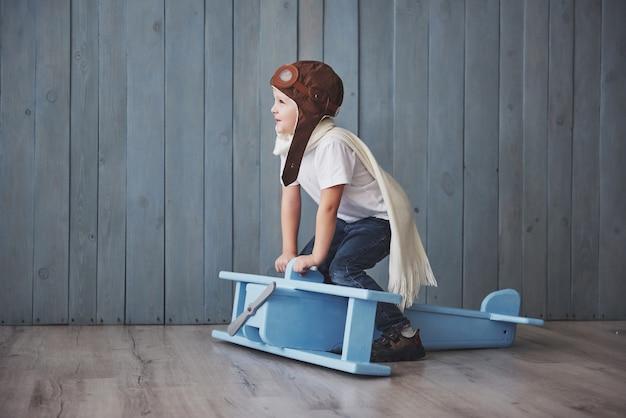 Szczęśliwy dzieciak w pilotowym kapeluszu bawić się z drewnianym samolotem przeciw. dzieciństwo. fantazja, wyobraźnia. wakacje Premium Zdjęcia